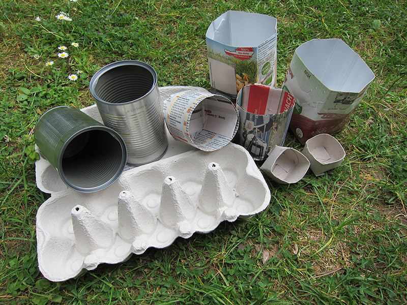 Eine Auswahl an möglichen Anzuchtgefäßen: Dosen, Eierkartons, Zeitungspapier, Getränkekartons und Klopapierrollen.