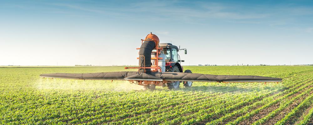 Traktor versprüht Pestizide über Sojafeld