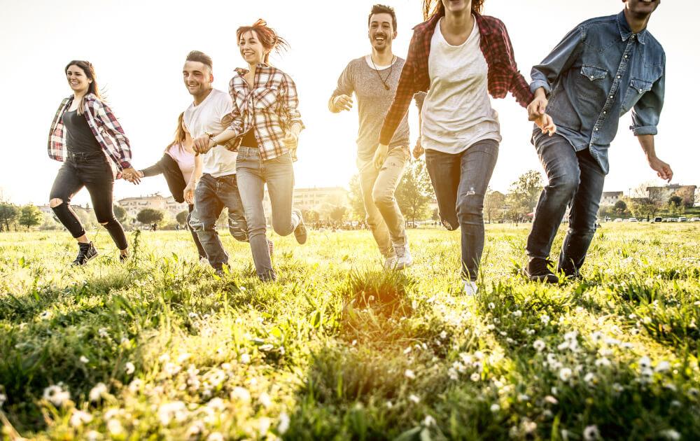 Jugendliche auf Wiese gemeinsam für den Umweltschutz (c) oneinchpunch / Shutterstock