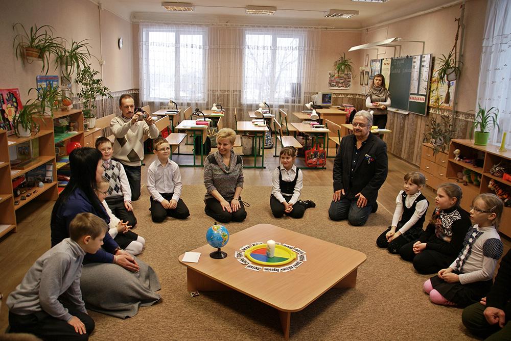Kinder sitzen im Kreis um Geburtstag zu feiern.