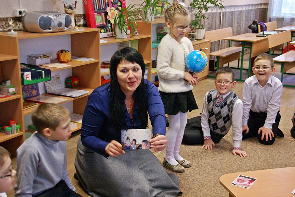 Kinder sitzen im Kreis für Montessori-Geburtstagsfeier.