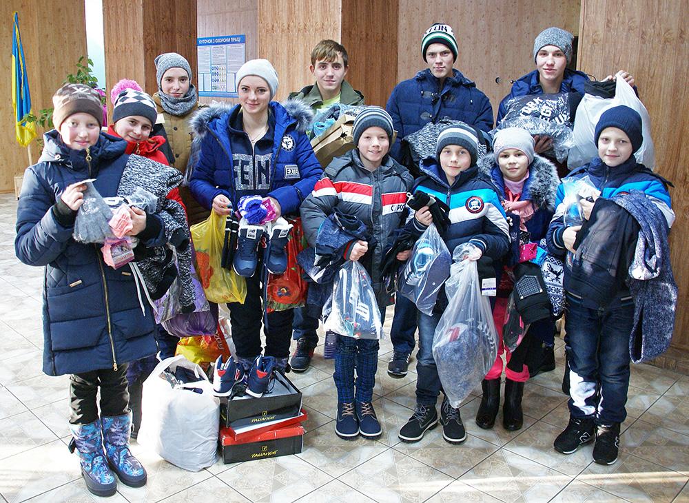Die Kinder sind glücklich über die neue Winterkleidung und Schuhe.