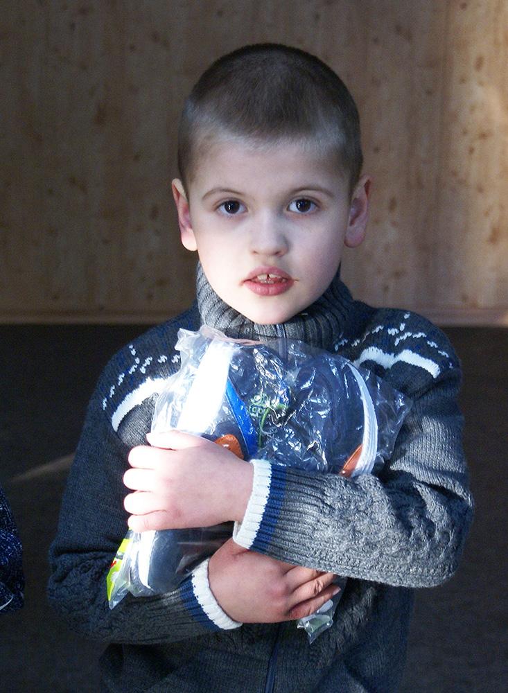 Kind hält die neue Winterkleidung in Händen.