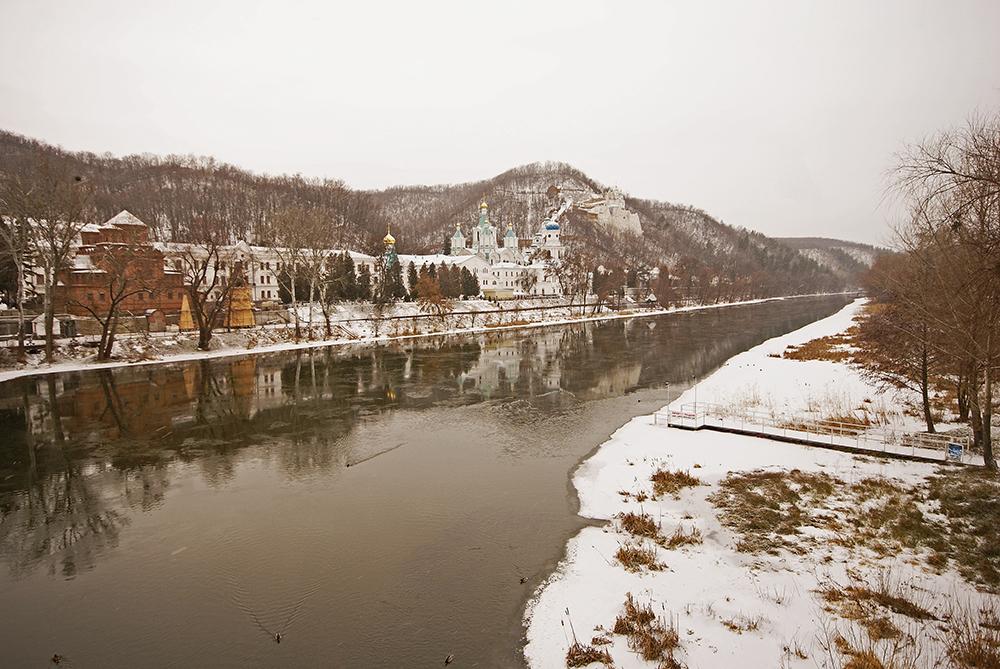 Fluss in Svyatogorsk mit Kloster im Hintergrund, dahinter Gebirge.