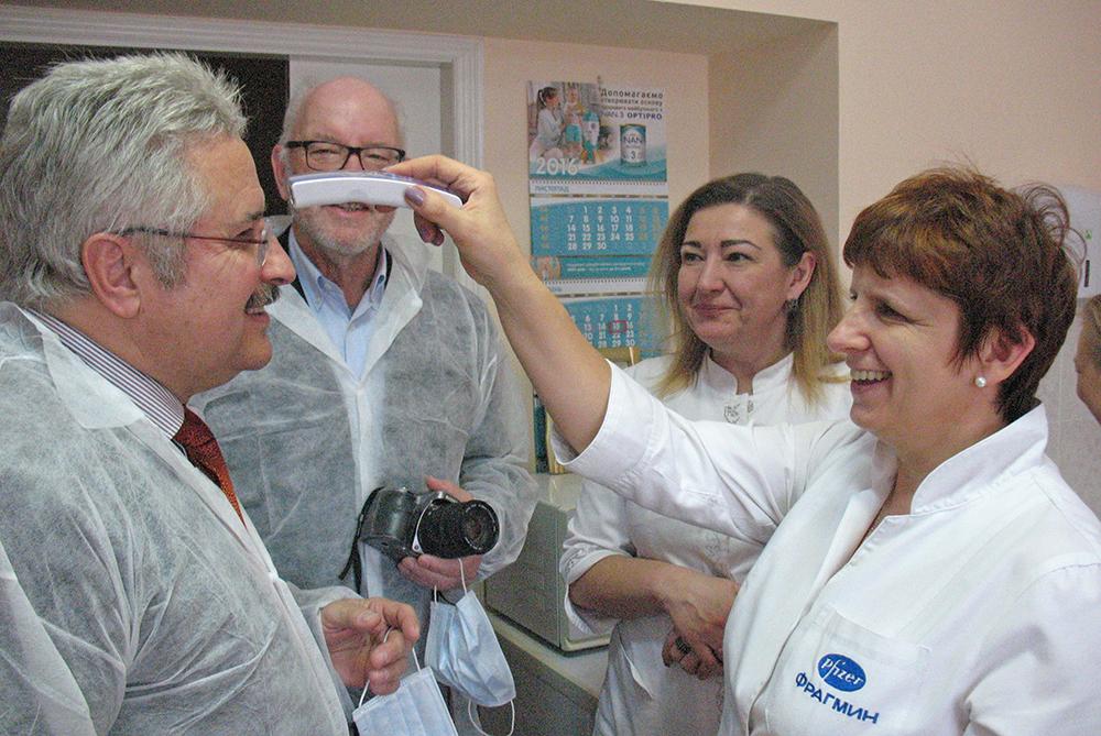 Die Ärztin Ludmilla Marenych im Kinderkrankenhaus probiert die soeben übergebenen Stirnthermometer an Christoph Otto aus.