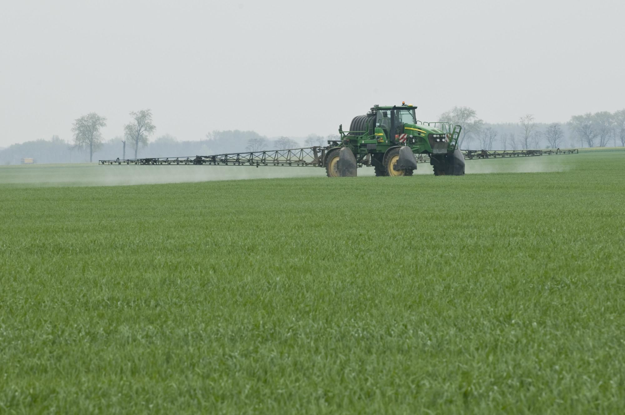 Traktor der Pestizide am Feld ausbringt