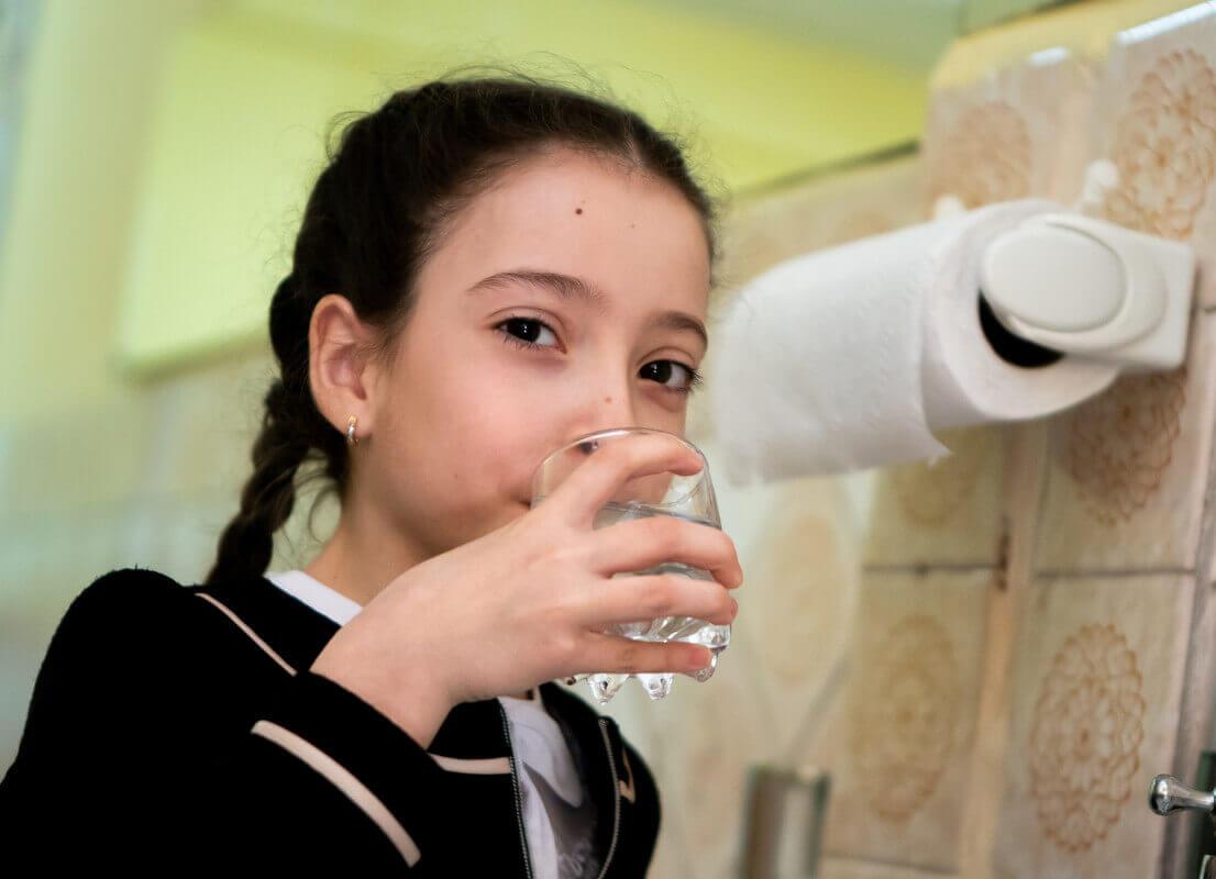 Kind mit frischem Trinkwasser