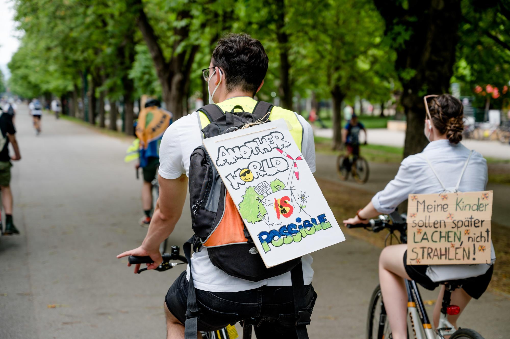 """Aufnahme von zwei DemonstrantInnen mit Protestschildern am Rücken """"Another World is possible"""""""