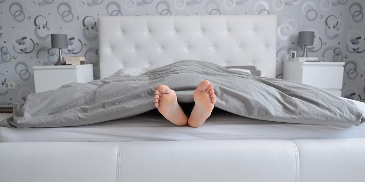 Schlafzimmer mit Füßen die aus dem Bett ragen