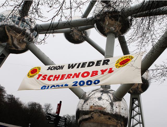 Am Atomium in Brüssel entrollen Aktivisten ein Banner gegen Atomkraft