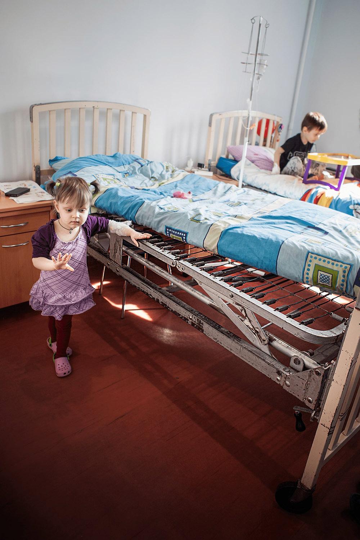 Tschernobyl-Kind neben altem Bett