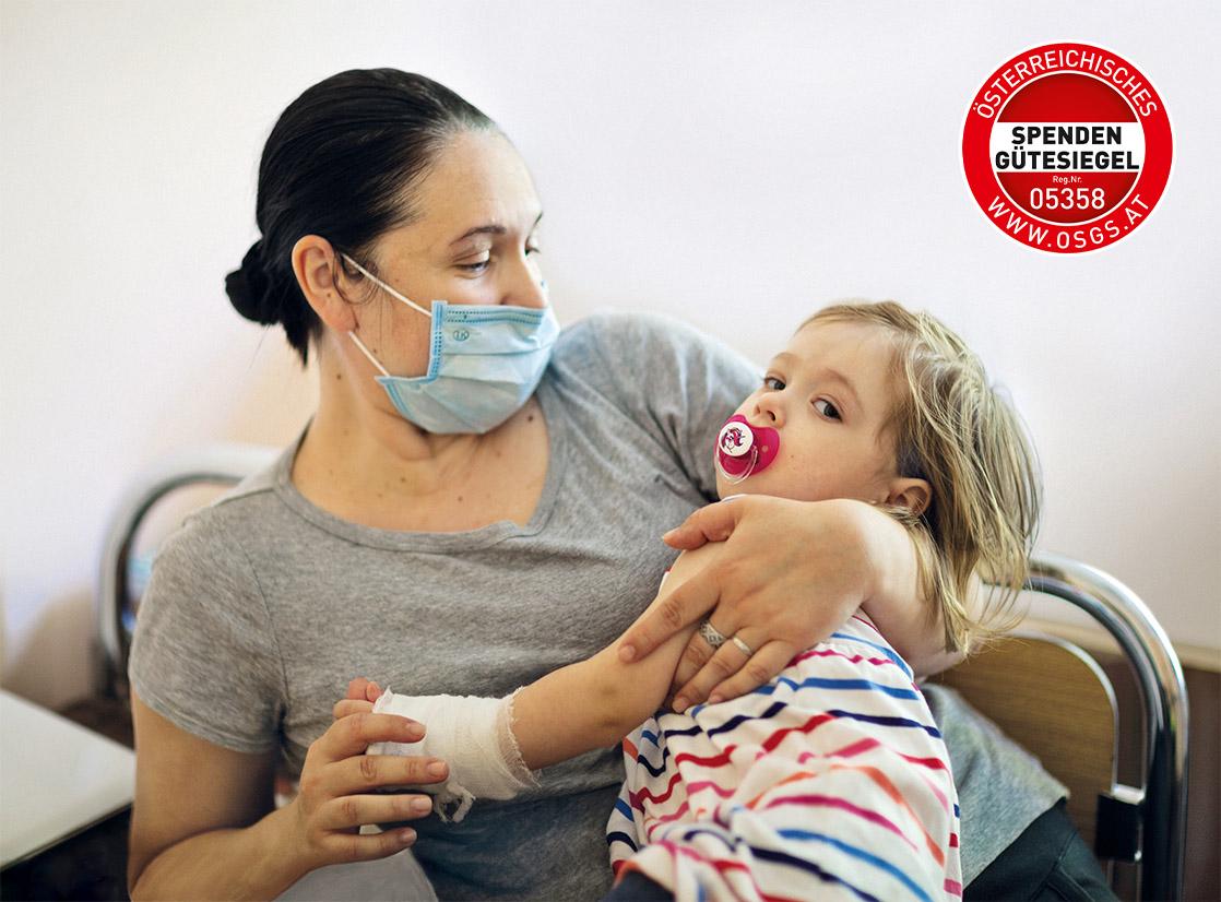 Tschernobylkind und Mutter mit Maske und Spendengütesiegel